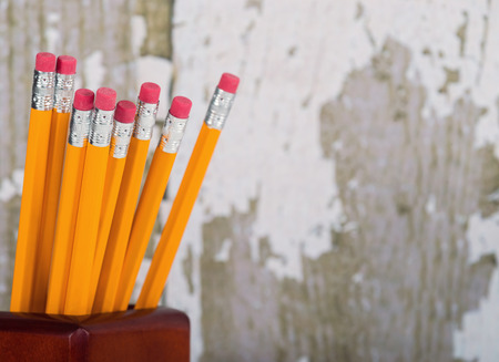Group of eraser ends of yellow pencils in pencil holder. Gray wooden background with copy space. Shallow depth of field.
