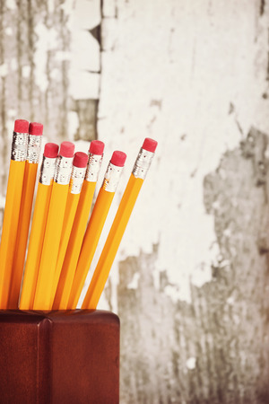 Group of eraser ends of yellow pencils in pencil holder, gray wooden background with copy space, vintage filter effects photo