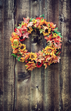 Autumn flower wreath against rustic wooden planks photo