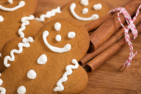 Freshly baked gingerbread man cookies with cinnamon sticks on wooden cutting board, closeup photo