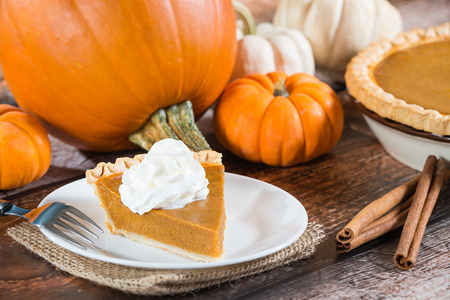 Slice of a pumpkin pie and pumpkins on wooden table Stock Photo