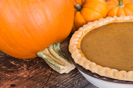 Closeup of pie pumpkin and a homemade pumpkin pie, wooden background photo