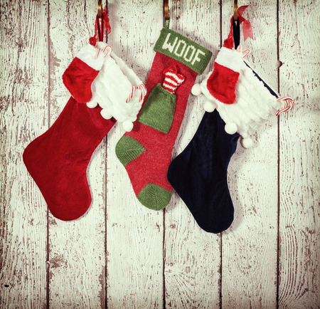 Christmas stocking hanging against rustic wood background. Vintage filter effects. Фото со стока