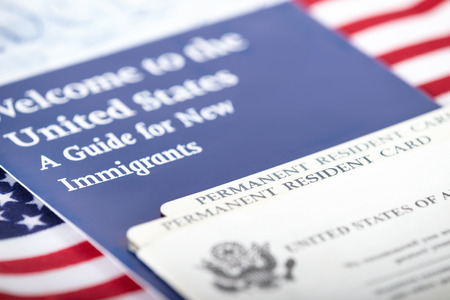 us government: United States of America social security and green card with US flag on the background. Immigration concept. Closeup with shallow depth of field.