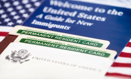 United States of America permanent resident cards, green card, with US flag on the background. Immigration concept. Closeup with shallow depth of field.
