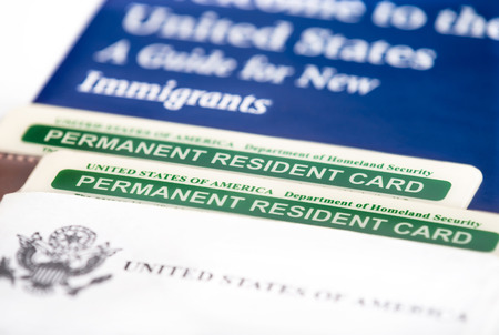 United States of America permanent resident cards, green card. Immigration concept. Closeup with shallow depth of field.