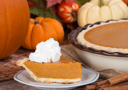 cream pie: Slice of a pumpkin pie with whipped cream on wooden table. Pie and pumpkins on the background.