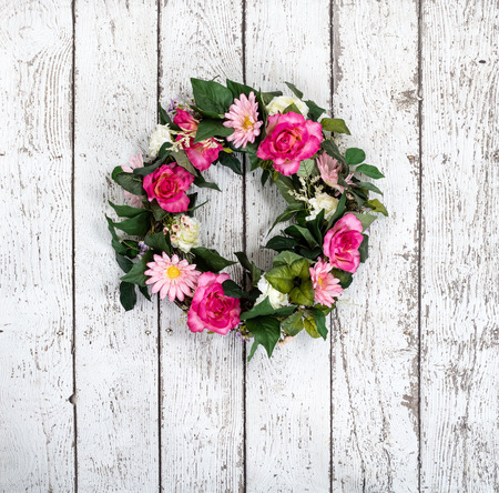 Flower wreath hanging against vintage white background