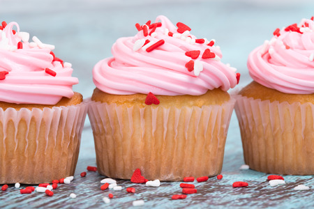 pink cake: Pink Valentines Day cupcakes with sprinkles on blue wooden vintage background