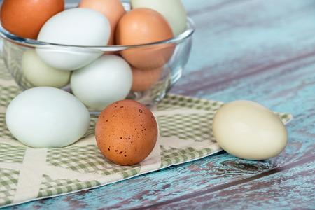 huevo: Surtido de diferentes colores, huevos de gallina frescos en un taz�n de vidrio, fondo verde de cosecha Foto de archivo