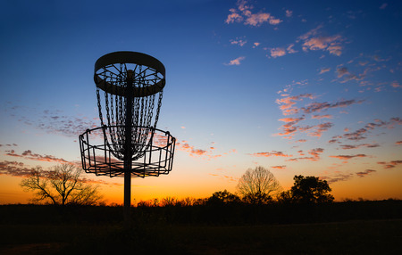 disc golf: Silhouette of disc golf basket in the park at sunset