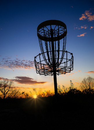 Disc golf basket in the park at sunset or sunrise photo