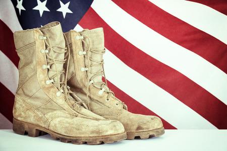 estrellas  de militares: Botas de combate viejos con la bandera americana en el fondo. Efecto de filtro de la vendimia.