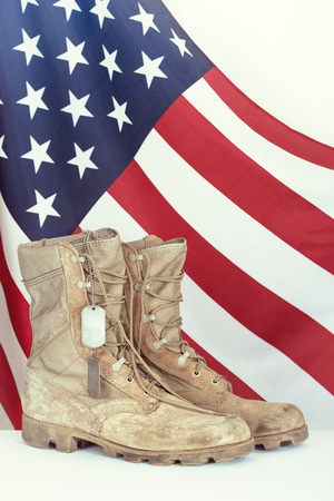 estrellas  de militares: Botas de combate viejos y placas de identificación con la bandera americana en el fondo Foto de archivo