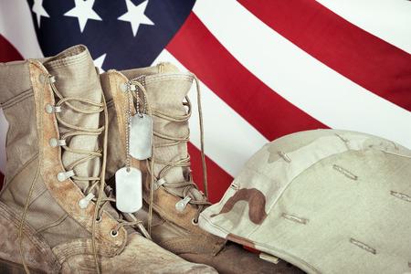 soldado: Botas viejas de combate, placas de identificación, y casco con la bandera americana en el fondo, de cerca Foto de archivo