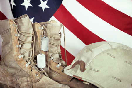 combat boots: Old combat boots, dog tags, and helmet with American flag in the background, closeup Stock Photo