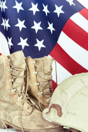 古い戦闘ブーツとヘルメット バック グラウンド、クローズ アップでアメリカの国旗と