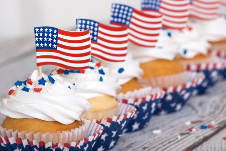 Row of patriotic cupcakes with sprinkles and American flags on vintage background