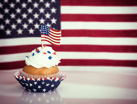 Patriotic 4th of July cupcake with American flag. Vintage filter effects. photo