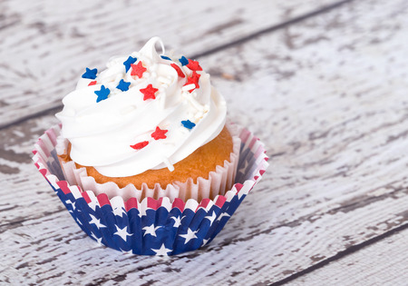 independence day: Cupcake with patriotic 4th of July sprinkles on vintage background