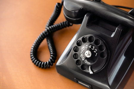 Old fashioned retro rotary dial phone on wooden desk, closeup Stock Photo