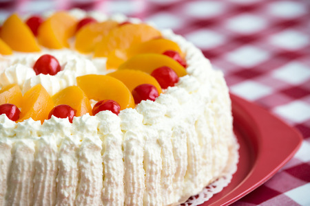 Homemade cream cake with peaches and cherries, closeup with shallow depth of field Standard-Bild