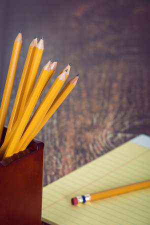 pencil holder: Group of yellow pencils in pencil holder. Notepad in the background on wooden vintage desk. Stock Photo
