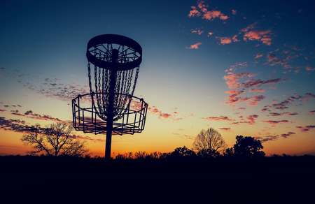 tree disc: Silhouette of disc golf basket against sunset. Vintage filter effects.