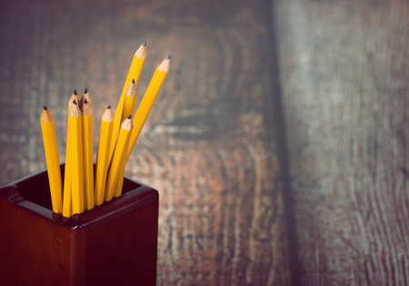 pencil holder: Group of yellow pencils in pencil holder. Vintage wooden background with copy space. Selective focus.