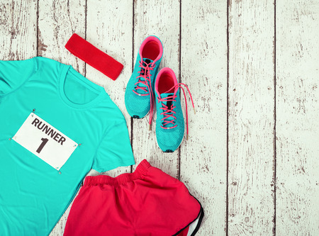 Running gear laid out ready for a race day, rustic wooden background with copy space