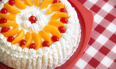 Homemade cream cake with peaches and cherries