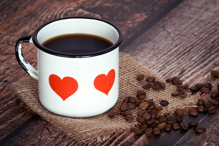 A cup of black coffee in an old enamel mug with hearts, coffee beans on vintage rustic background 免版税图像