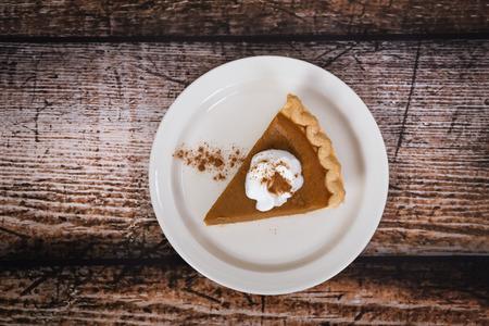 pumpkin pie: Slice of a pumpkin pie on wooden vintage table