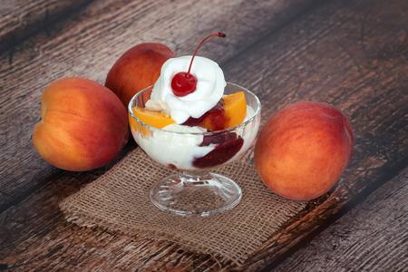 melba: Crema de vainilla melocot�n Melba hielo con fruta del melocot�n en el fondo de la cosecha de madera oscura