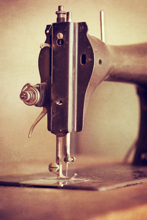Old sewing machine on textured vintage background, closeup