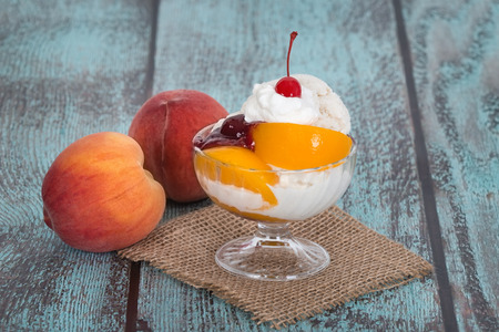 melba: Helado de vainilla melba melocot�n de hielo con frutas de durazno en el fondo de madera de �poca Foto de archivo
