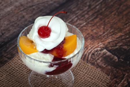 melba: Vanilla peach melba ice cream with whipped cream and a cherry, wooden dark vintage background