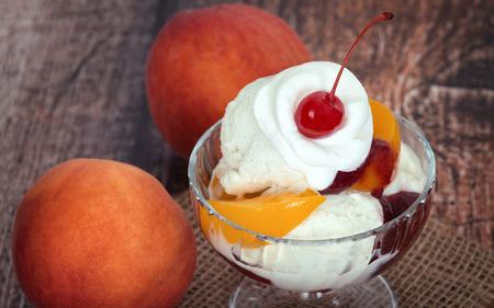 melba: Vanilla melba melocotón helado con crema batida y una cereza, madera fondo oscuro de la vendimia