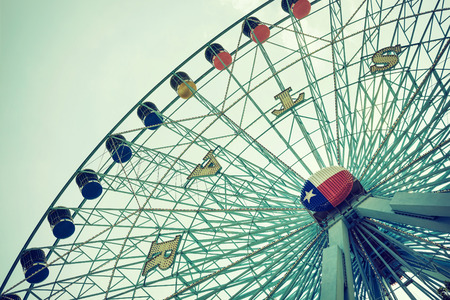 dallas: DALLAS, TX, - August 16, 2015: Texas Star, the largest ferris wheel in North America, rises above the horizon at Fair Park in Dallas, Texas. Closeup view. Vintage filter effects. Editorial