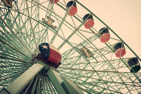 DALLAS, TX, - August 16, 2015: Texas Star, the largest ferris wheel in North America, rises above the horizon at Fair Park in Dallas, Texas. Closeup view. Vintage filter effects. Reklamní fotografie - 43722673
