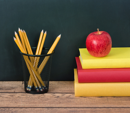pencil holder: Stack of school books with apple and pencils in pencil holder on the desk. Chalkboard in the background.