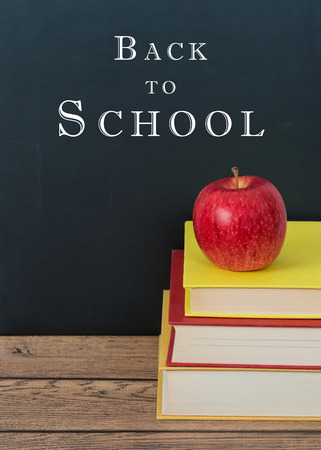 school board: Red apple on the stack of books. Chalkboard background with Back to School text.