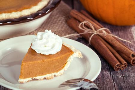 calabaza: Una rebanada de pastel de calabaza en la mesa de madera. Pie y palitos de canela en el fondo.