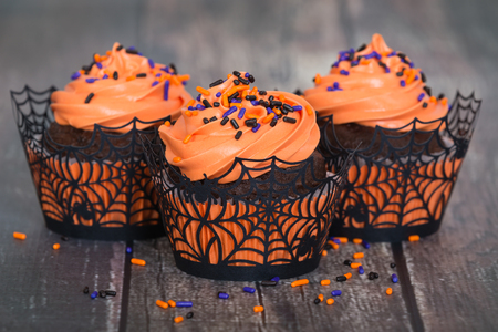 cupcakes: Festive Halloween cupcakes with sprinkles on vintage wooden background