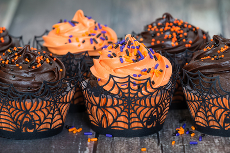 Orange and dark chocolate Halloween cupcakes against rustic background