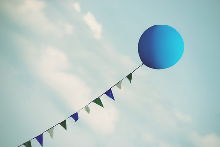 Blue balloon floating in the blue sky with white clouds. Vintage filter effects.