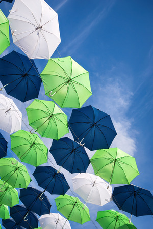 umbrella: Group of green, blue, and white umbrellas against blue sky Stock Photo