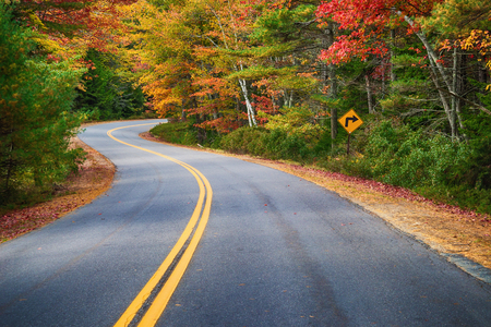 drives: Winding road curves through colorful autumn trees in New England Stock Photo