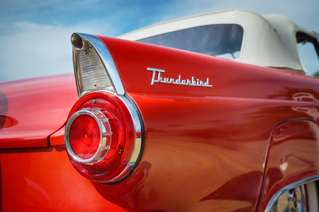ford: WESTLAKE, TEXAS - OCTOBER 17, 2015: Tail fin and taillight details of a red 1956 Ford Thunderbird Convertible classic car.