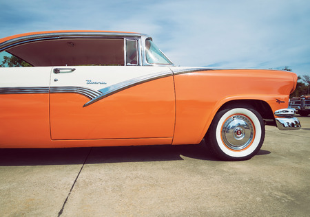 white car: WESTLAKE, TEXAS - OCTOBER 17, 2015: Front side view of a mandarin orange and white 1956 Ford Victoria classic car.